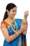 Молодая традиционная индийская женщина смотря bangles против белизны Стоковые Фотографии RF