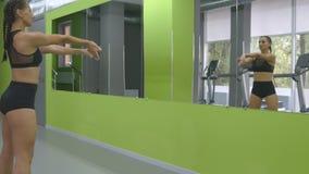 Молодая тренировка женщины фитнеса перед зеркалом на спортзале Спортсменка протягивая ее тело и руки раньше Стоковая Фотография RF