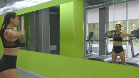 Молодая тренировка женщины фитнеса перед зеркалом на спортзале Спортсменка протягивая ее тело и руки раньше видеоматериал