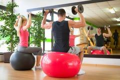 Молодая тренировка пар в спортзале с гантелями перед зеркалом Стоковая Фотография
