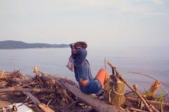 Молодая туристская женщина в джинсах куртке и рубашках наслаждаясь видом на море Стоковое фото RF