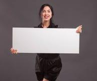 Молодая уверенно женщина показывая представление, указывая на плакат стоковое фото rf