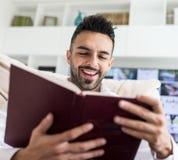 Молодая уверенно книга чтения человека стоковое изображение