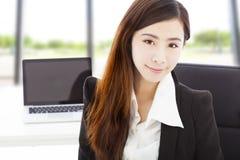 Молодая уверенно коммерсантка сидя в ее офисе стоковые изображения