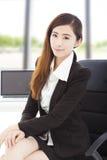 Молодая уверенно коммерсантка сидя в ее офисе стоковая фотография rf