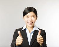 Молодая усмехаясь бизнес-леди с большим пальцем руки вверх показывать Стоковое Изображение RF