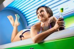 Молодая усмехаясь девушка брюнет лежа в солярии Стоковые Изображения RF