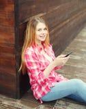 Молодая усмехаясь девушка используя усаживание smartphone стоковые изображения
