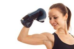 Молодая усмехаясь девушка напрягла мышцу в наличии в перчатке бокса на белой предпосылке Стоковая Фотография