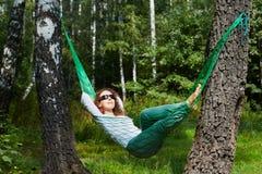 Молодая усмехаясь женщина в темных солнечных очках лежит в гамаке стоковая фотография