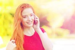 Молодая усмехаясь женщина говоря на мобильном телефоне Стоковая Фотография RF
