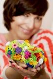 Молодая усмехаясь женщина держа в пасхальном яйце рук 2 красочном Стоковая Фотография RF