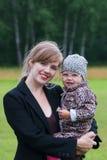 Молодая усмехаясь женщина держит маленькую милую дочь Стоковое Фото