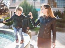 Молодая усмехаясь женщина и маленькая счастливая девушка Стоковое Фото