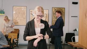 Молодая усмехаясь женщина идя через офис и используя умный вахту app Девушка смотря время движение медленное видеоматериал