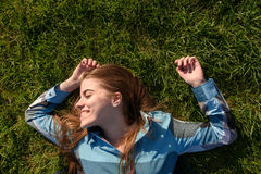 Молодая усмехаясь женщина кладя в траву Стоковые Фотографии RF