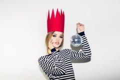 Молодая усмехаясь женщина празднуя партию, нося обнажанное платье и красную бумажную крону, счастливый динамический шарик диско м Стоковое Фото