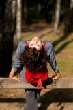 Молодая усмехаясь женщина сидя на загородке Стоковые Изображения