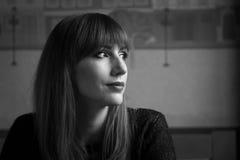 Молодая усмехаясь женщина смотря через окно в кафе Стоковые Фото