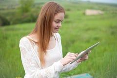 Молодая усмехаясь женщина с компьтер-книжкой в парке Стоковое фото RF