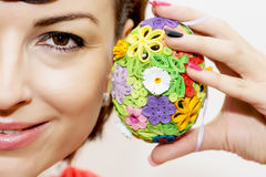 Молодая усмехаясь женщина с красочным пасхальным яйцом стоковое фото rf