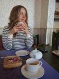 Молодая усмехаясь женщина с чашкой чая в руке Кафе Стоковое Фото
