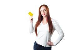 Молодая усмехаясь женщина redhead держа кредитную карточку золота Стоковые Изображения