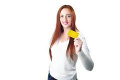 Молодая усмехаясь женщина redhead держа кредитную карточку золота Стоковая Фотография