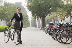Молодая усмехаясь коммерсантка держа велосипед на тротуаре, Пекине Стоковые Изображения