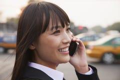 Молодая усмехаясь коммерсантка используя телефон снаружи на улице в Пекине, конце вверх по портрету Стоковые Фото