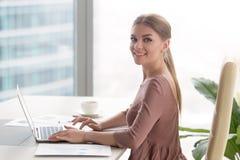 Молодая усмехаясь коммерсантка сидя на столе офиса смотря ca Стоковое фото RF