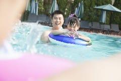Молодая усмехаясь семья брызгая и играя в бассейне Стоковое Фото