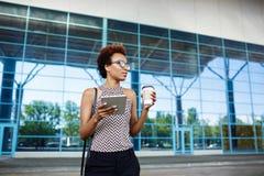 Молодая успешная африканская коммерсантка в стеклах стоя близко бизнес-центр Стоковые Изображения RF