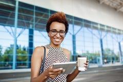 Молодая успешная африканская коммерсантка в стеклах стоя близко бизнес-центр Стоковая Фотография