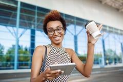 Молодая успешная африканская коммерсантка в стеклах стоя близко бизнес-центр Стоковое фото RF