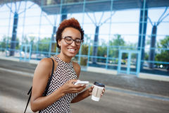 Молодая успешная африканская коммерсантка в стеклах стоя близко бизнес-центр Стоковое Изображение RF