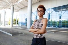 Молодая успешная африканская коммерсантка в стеклах стоя близко бизнес-центр Стоковая Фотография RF