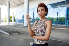 Молодая успешная африканская коммерсантка держа стекла, стоя близко бизнес-центр Стоковые Фото