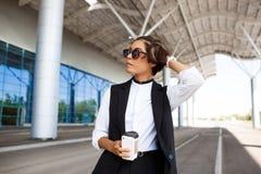 Молодая успешная коммерсантка в солнечных очках стоя близко бизнес-центр Стоковое Изображение RF