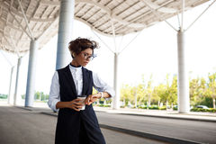 Молодая успешная коммерсантка смотря вахту, стоя близко бизнес-центр Стоковое Изображение