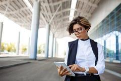 Молодая успешная коммерсантка смотря таблетку, стоя близко бизнес-центр Стоковое Изображение