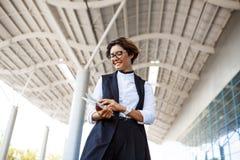Молодая успешная коммерсантка смотря таблетку, стоя близко бизнес-центр Стоковое Изображение RF