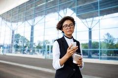 Молодая успешная коммерсантка смотря телефон, стоя близко бизнес-центр Стоковые Фото