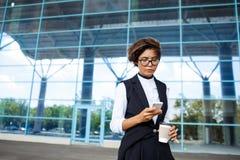 Молодая успешная коммерсантка смотря телефон, стоя близко бизнес-центр Стоковые Изображения