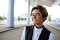 Молодая успешная коммерсантка усмехаясь, стоя близко бизнес-центр Стоковое Изображение RF