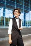 Молодая успешная коммерсантка усмехаясь, стоя близко бизнес-центр Стоковые Изображения RF