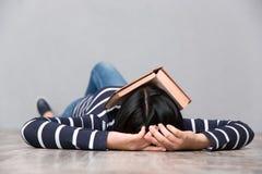 Молодая утомленная женщина спать с книгой на ее стороне стоковое изображение