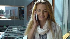 Молодая худенькая женщина использует smartphone в торговле и центре офиса движение медленное сток-видео