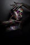 Молодая художническая женщина в черной краске и красочном порошке Накаляя темный состав Творческое искусство тела на теме космоса Стоковая Фотография