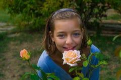 Молодая цыганская девушка обнюхивая розовый цветок Стоковое фото RF